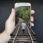 Mann geht auf Bahngleisen, die in ein Smartphone-Display reinragen, welches von einer männlichen Hand vorgehalten wird